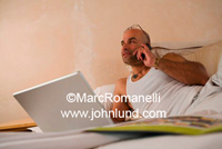 Picture of a man laying on a bed at home and using a cell phone for communications for his business. The man is hispanic, dressed all in white, and has glasses pushed up over his head